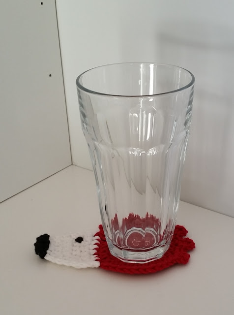 A standard glass tumbler rests on the red, white and black hedgehog coaster on a white desk.