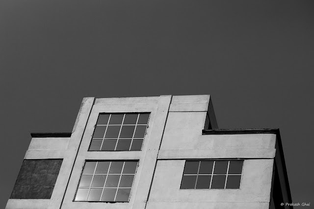 A Black and White Minimal Art Photograph of a Building with Three Windows