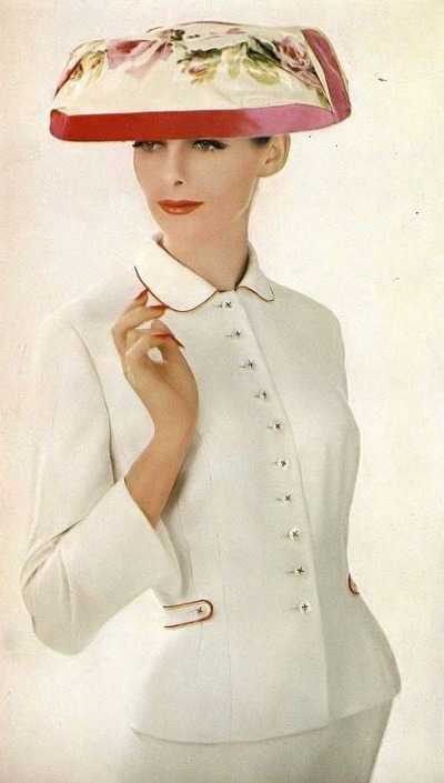Model Anne St.  Marie wearing white suit and flowered hat in Lillian Bassman photo for Harper's Bazaar