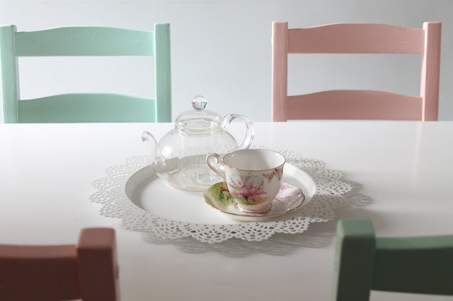 white dining room table pink and green chairs with teacup and clear teapot