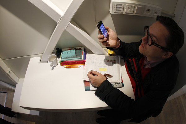 Picture of person sitting by the working desk in the world's narrowest house