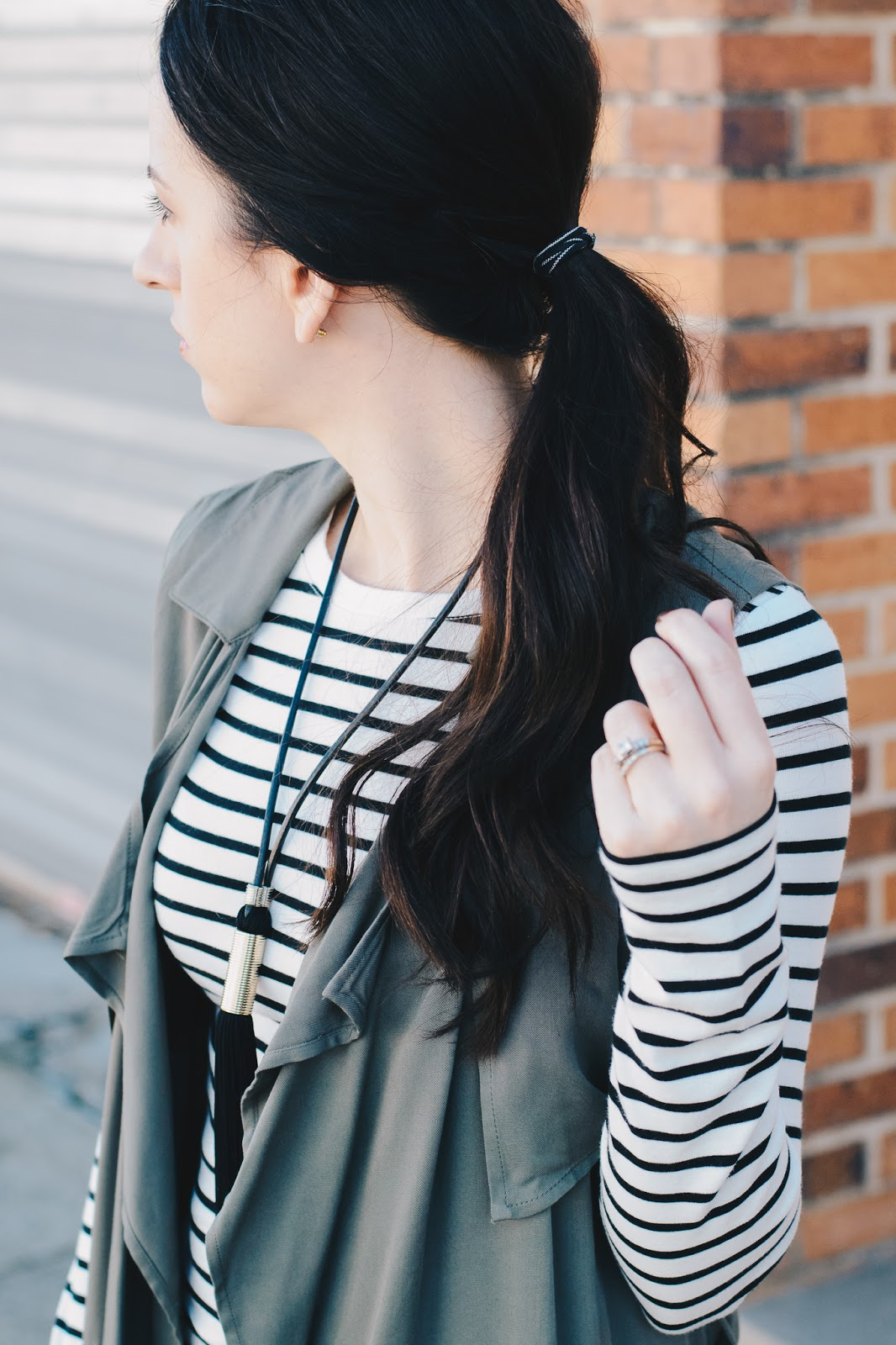 Curled ponytail paired with striped tee and tassel necklace