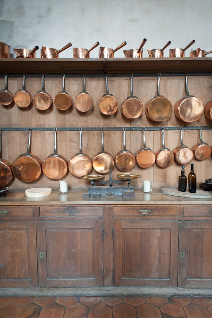 The kitchen in Vaux Le Vicomte Castle Outside Paris in Maincy France with dozens of copper pots on a top shelf and copper pans hanging on the wall above the counter