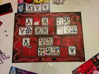 A view of the game board during a game in progress. The board consists of a scoring track around the edge, stylised to resemble a looped strand of DNA, with each 'space' made up of a section of the DNA between twists. The rest of the board is covered with twenty five spaces on which cards can be placed, overlaid on an image of the world map in red, grouped by continent: three spaces for North America, four spaces for South America, five spaces each for Europe, Asia, and Africa, and three spaces for Oceania. There are several Country cards on the board (only seven spaces are empty in total). These cards are marked with clusters of varying numbers (from three to seven) of hexagonal icons, with the icons on some of them marked with a sun symbol or a snowflake symbol. Most of the hexagonal icons are occupied by a plastic token, also hexagonal, in one of five colours: blue, green, red, yellow, or purple. Above the game board can be seen part of a play mat which contains several types of cards: a stack of yellow Event cards, a stack of red Trait cards, a stack of blue Country cards, and three additional country cards face up waiting to be chosen. Around the board can be seen some additional components (claimed or discarded Country cards, more plastic tokens, the Death Die—a standard six-sided die, white with red flecks—and portions of players' Evolution Slide play mats).