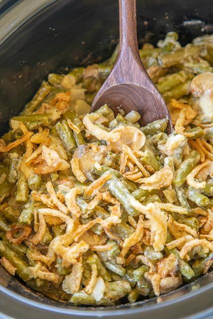 Slow Cooker Green Bean Casserole - no cream of anything soup!! Green beans, alfredo sauce, water chestnuts, mushrooms, parmesan cheese, pepper and french fried onions. Seriously delicious!! Everyone raved about this yummy side dish. Perfect for Thanksgiving and Christmas dinner! A real crowd pleaser! #crockpot #slowcooker #sidedish #thanksgivingsidedish #christmassidedish