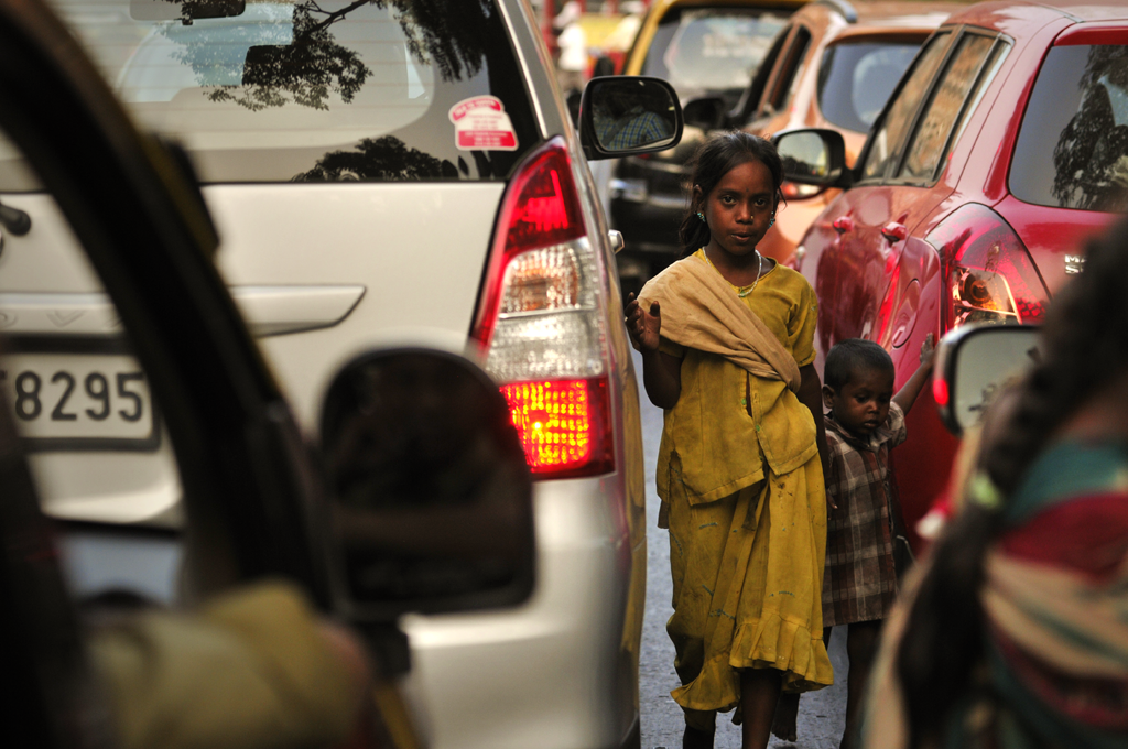 Street girl with a younger child at her side.