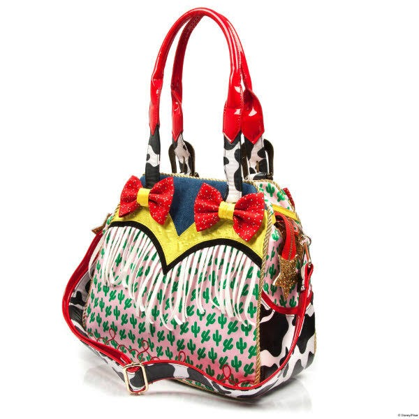 back view of large tote bag with red bow and white fringing trim, in denim, yellow and cactus materials with long detachable cow print strap