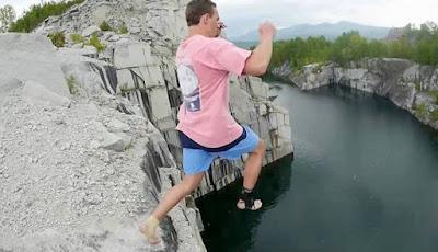 Pria terjun dari tebing tinggi ke dalam air.