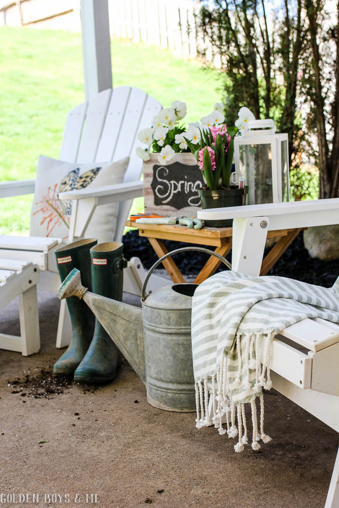 White Adirondack chairs with spring items under covered patio