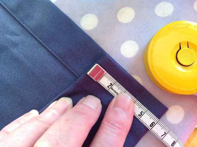 Hand holding hem and tape measure