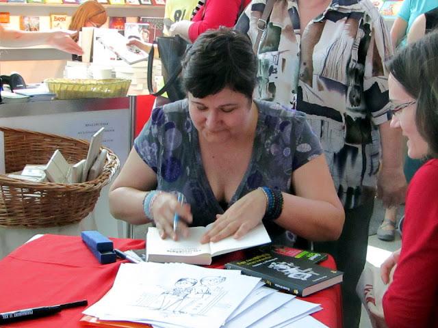 Ecsédi Orsolya dedikálja Cirrus a Tűzfalon című ifjúsági regényt, a Budapesti Nemzetközi Könyvfesztivál Gyerek(b)irodalom Könyvmolyképző standján.