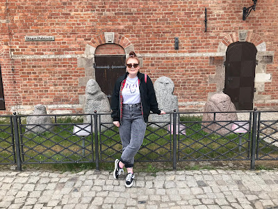 me standing in front of 4 prussian hag statues in Gdansk