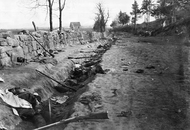 Confederate dead lie among rifles and other gear, behind a stone wall at the foot of Marye's Heights near Fredericksburg, Virginia on May 3, 1863. Union forces penetrated the Confederate lines at this point, during the Second Battle of Fredericksburg.