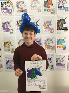 10 year old boy holds picture he's colored for pride fest in front of backdrop of other coloring pages