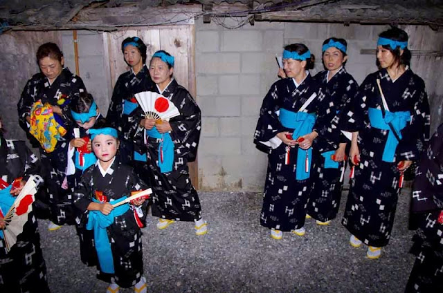 young girls in kimonos dance at night