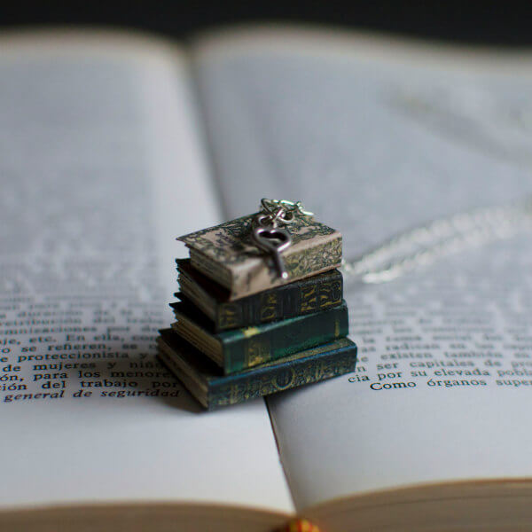 four tiny paper books with metal key charm on silver necklace chain
