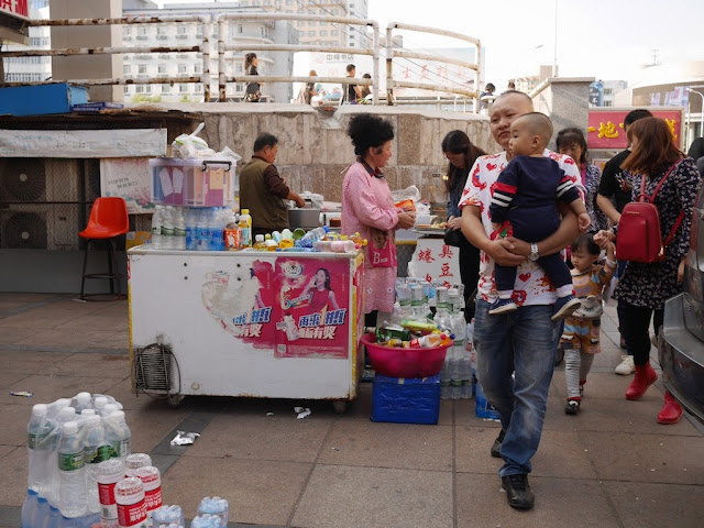 man carrying a boy past street vendors in Mudanjiang, China