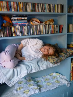 My daughter lying on a shelf with a blanket and cushion, on moving day when we moved to the country