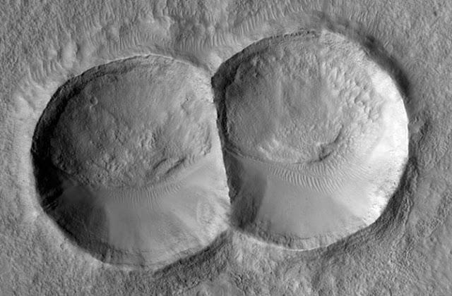 Miệng hố va chạm đôi được tạo ra do thiên thạch tách đôi trước khi rơi xuống bề mặt. Gió mạnh làm xói mòn và khiến một nửa của hai miệng hố trở nên rất mịn màng. Hình ảnh: NASA/JPL.