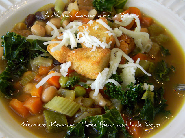 Bowl of soup with celery, carrots, beans, kale, shredded cheese and croutons.