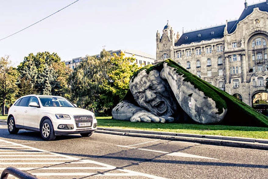 A Giant Sculpture Crawls Out Of The Ground In Public Square Of Budapest