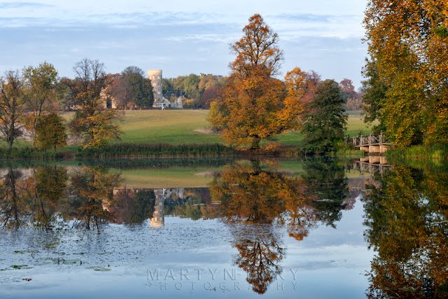 Wimpole Estate lake and autumn trees are reflected in the still water