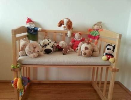 Babybett umgebaut als Bank mit Kuscheltieren darauf