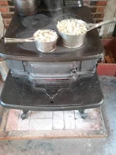 Two tin pans of apples boiling on a wood-burning stove.