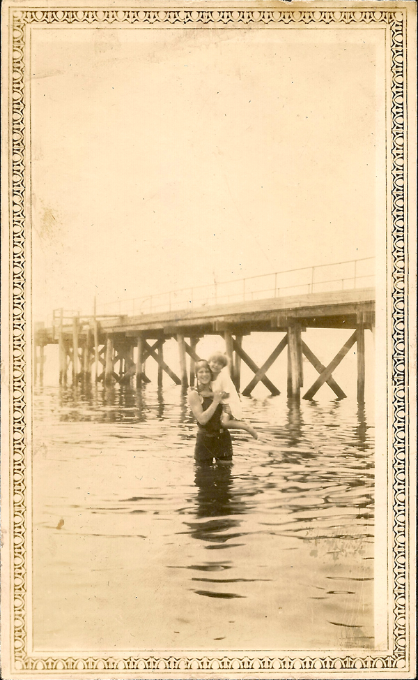 Photo of a young woman wading in water, holding a girl. Standing in front of a pier.