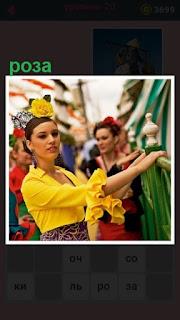 стоит женщина в желтой кофточке и с желтой розой в волосах