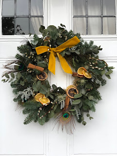 Christmas wreath hanging on a white front door