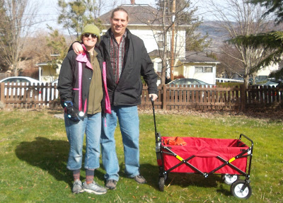 Cynthia M. Parkhill and Jonathan L. Donihue standing in grassy fenced yard holding the handle of a red wagon that is shown in side-view