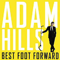 Best Foot Forward audiobook cover. Wearing a black suit, Adam poses with a mic stand, in front of a solid yellow background.
