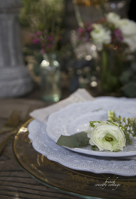 white ranunculus flower on blue dishes on table setting