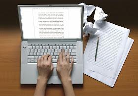 imagem de um notebook com duas mãos em cima digitando um documento,  folhas de papel do lado com um lápis em cima, atras do notebook papeis amassados