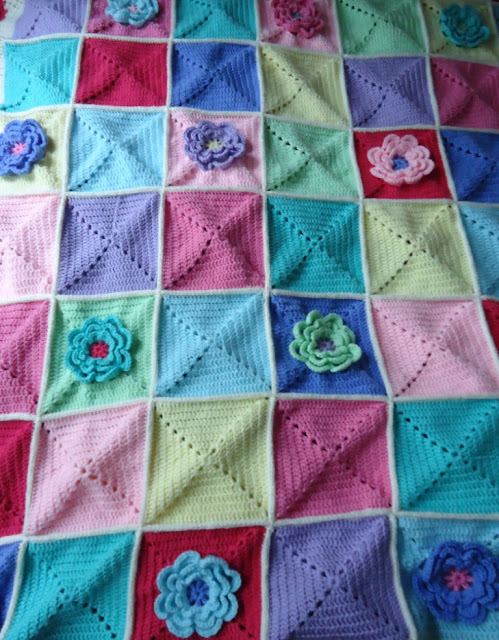 A beautiful colourful crochet blanket with a lovely waterlily design - click through for inspiration for a stunning cosy flower crochet blanket.