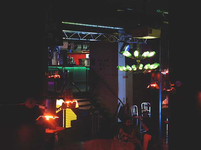 a dark bar lite by bright bottles and low orange lights