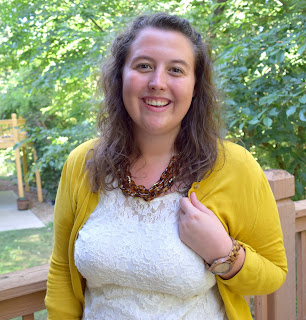 a woman wearing a lace shirt, a mustard cardigan, a tortoiseshell necklace, navy pants, and mustard flats