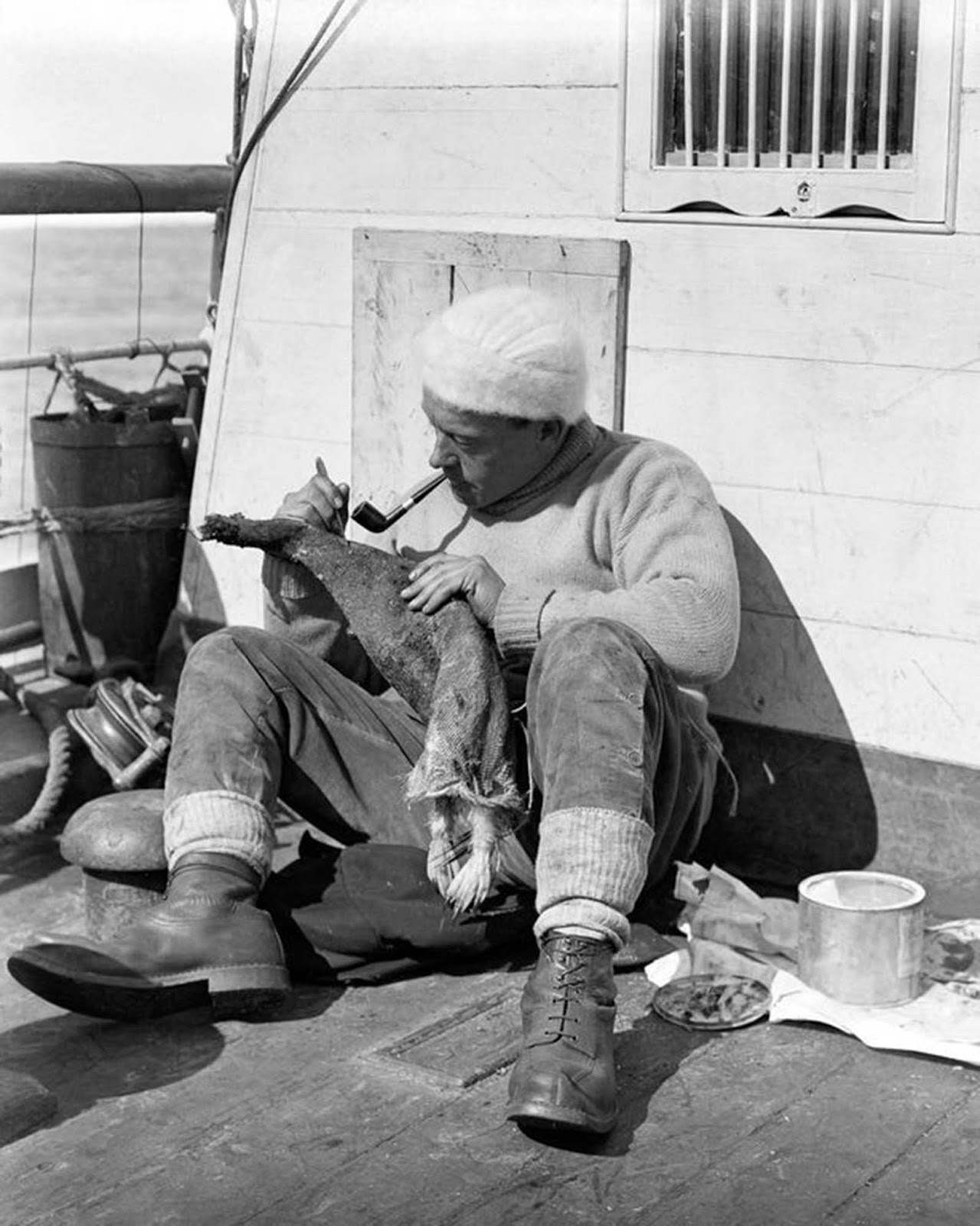 Ship's surgeon George Murray Levick skins a penguin on the deck of the Terra Nova. 1910.