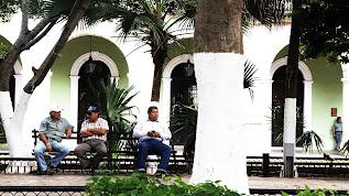 Three older gentlemen sit on a park bench in Plaza Grande in Merida, Mexico