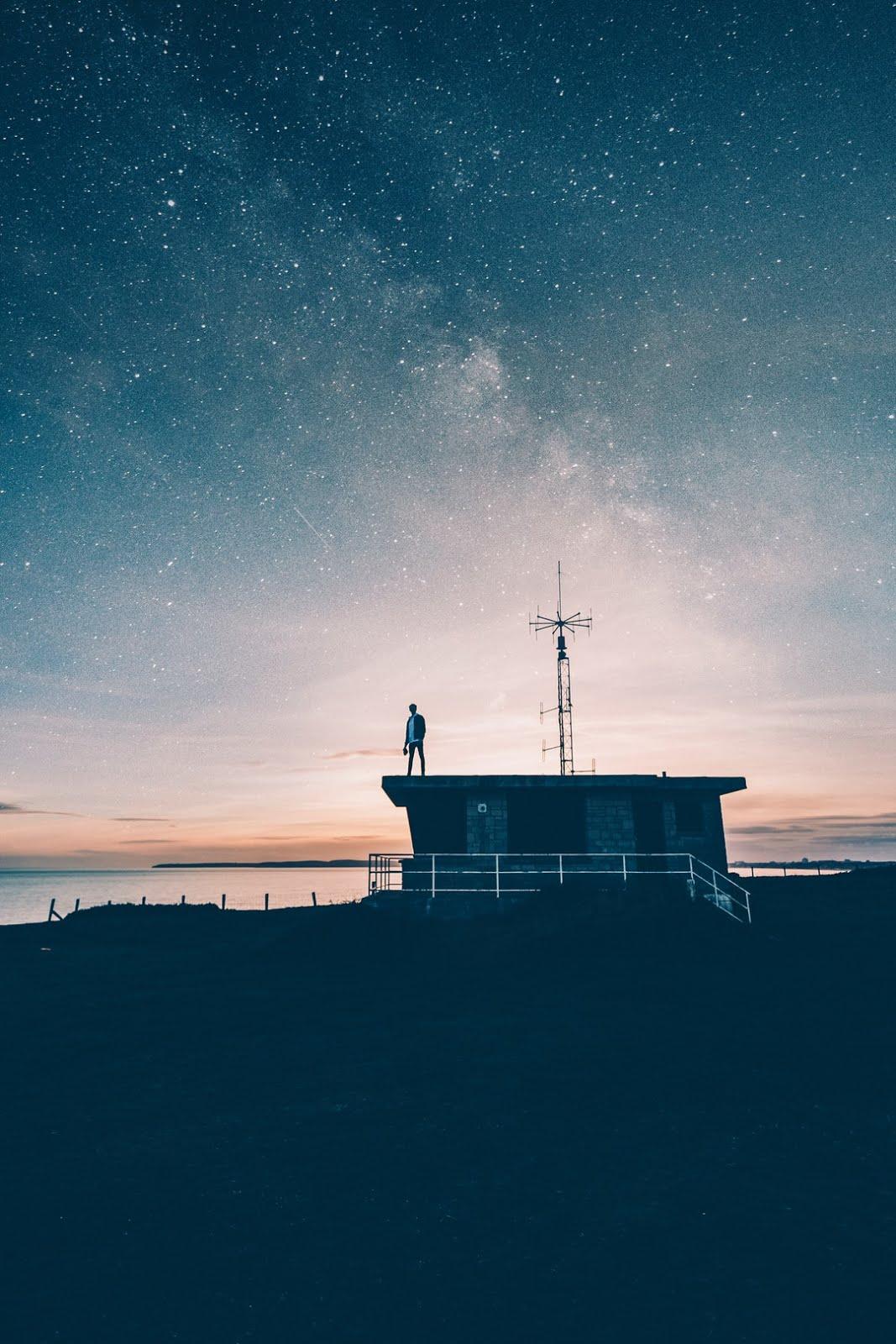 رجل يقف فوق مبني امام العديد من المجوم الساطعة خلفيات ايفون 6s