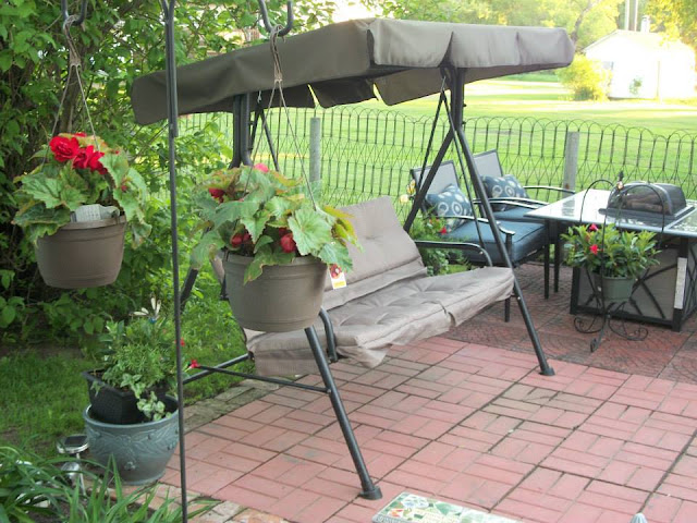 swing and hanging  flowers by swing on brick patio