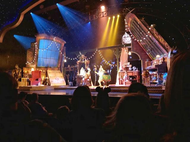 Escenario lleno de color, luces y mágia donde se ve a Mickey con Rafiki