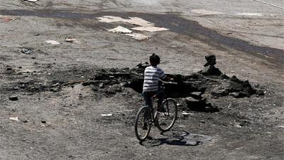 Un muchacho pasa en bicicleta junto al cráter dejado por un ataque aéreo en la ciudad de Dael (Siria).Alaa FaqirReuters