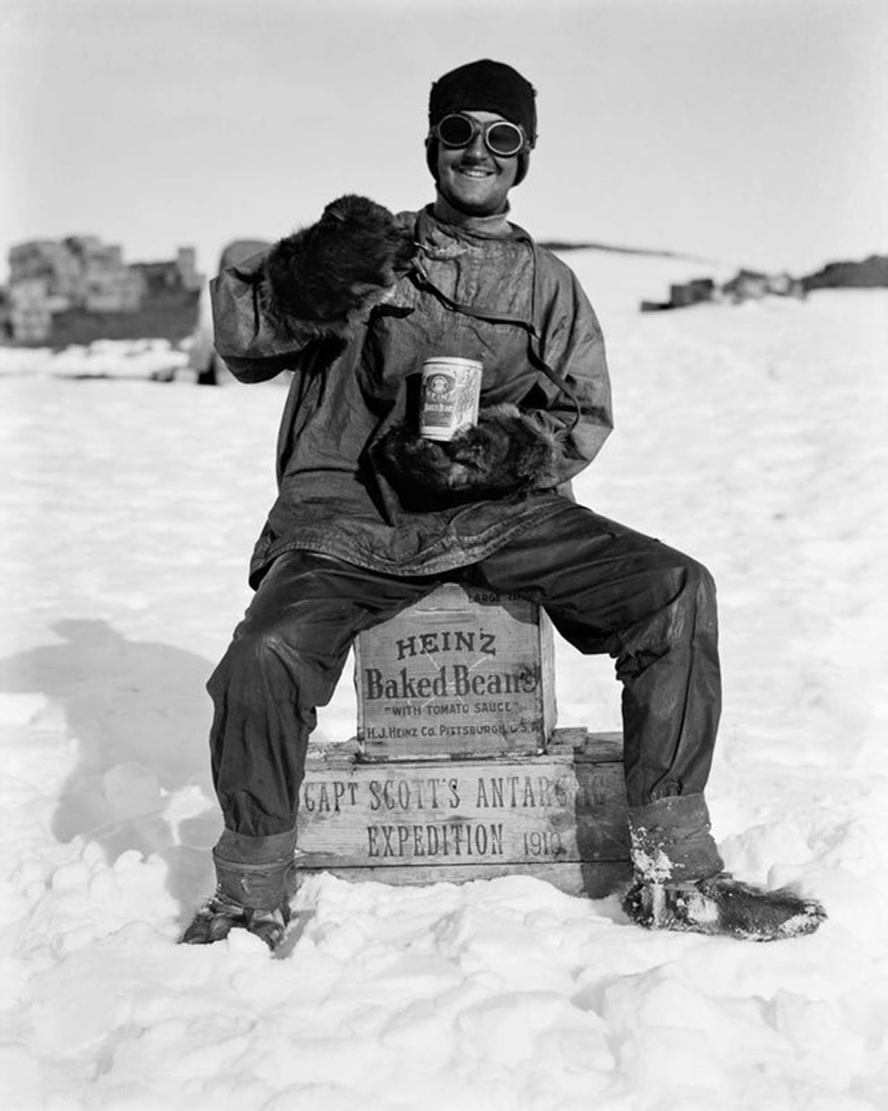 An expedition member enjoys a can of beans at camp. January, 1912.