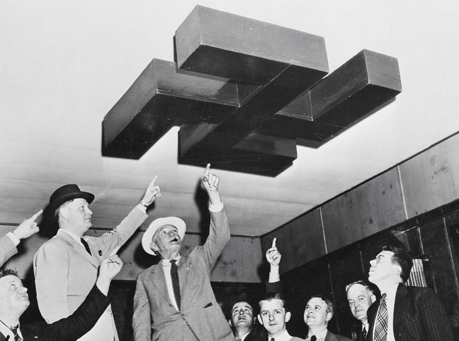 Original caption: Andover, New Jersey: Bund Camp Raided. Sheriffs Deputies who assisted Sheriff Denton J. Quick, of Sussex County in raid on German American Bund Camp Nordland at Andover, New Jersey, shown examining swastika decoration on ceiling of one of the assembly halls at the camp.