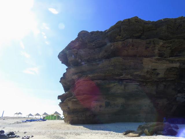 Núi đá lồi lõm tầng lớp nối giữa bãi cái trắng và trời xanh tạo cảnh tượng hùng vĩ.