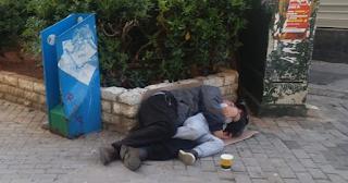 Πατέρας και γιος κοιμούνται αγκαλιά σε πεζόδρομο Μεγάλη Εβδομάδα στον Πειραιά