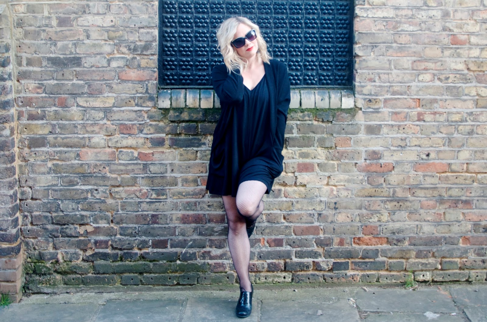Black romper, black cardigan, black sunglasses with gold spikes, fishnet tights and brogues
