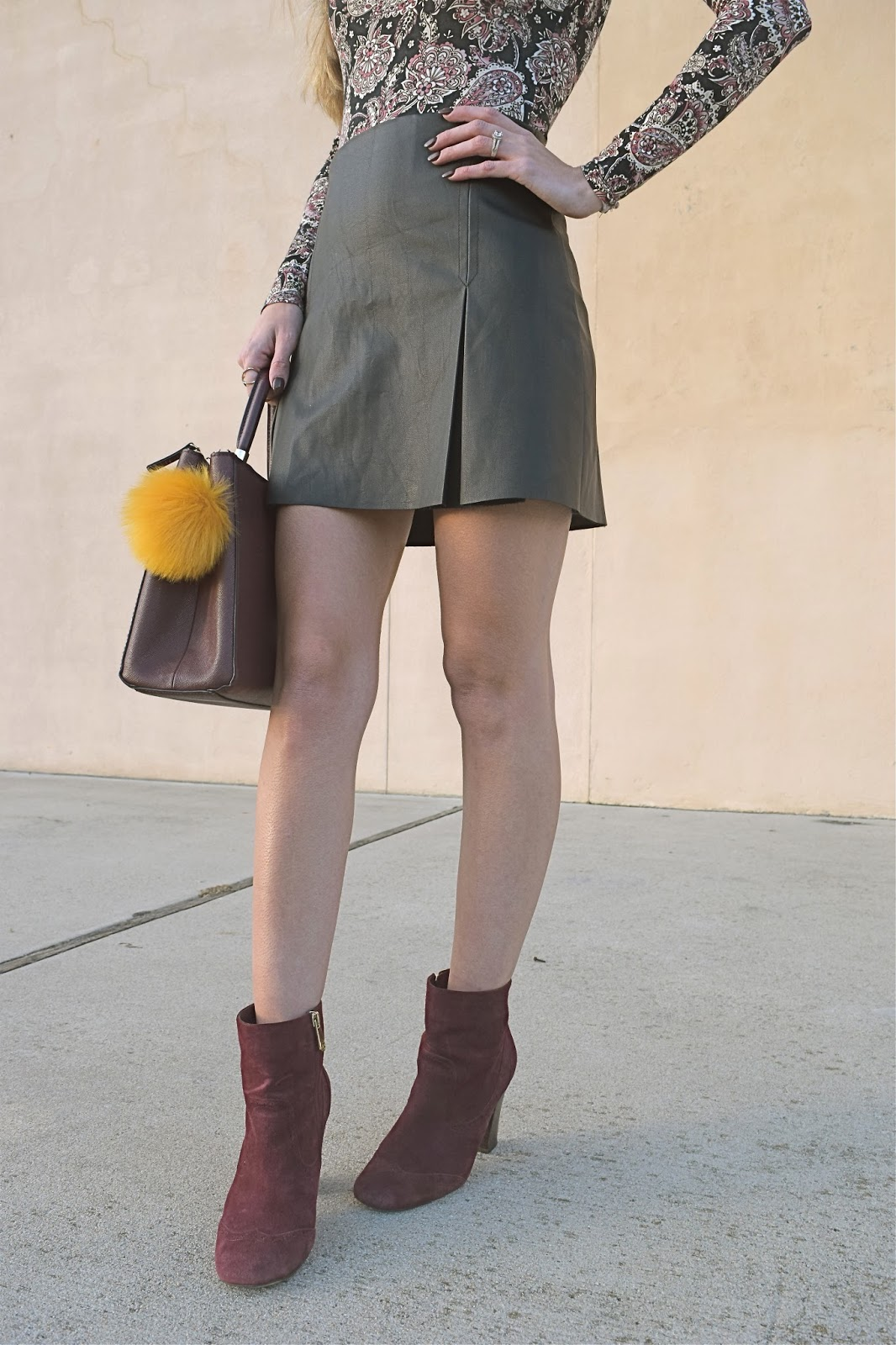 wearing Target bodysuit, cold shoulder body suit, express pleated leather mini skirt, wearing burgundy suede booties, h&m burgundy bag with fur ball